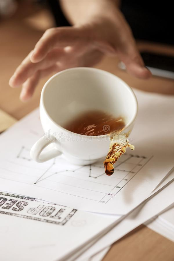 Coffee in white cup spilling on the table in the morning working day at office table. The male hands and coffee in white cup spilling in slow motion or movement stock photos