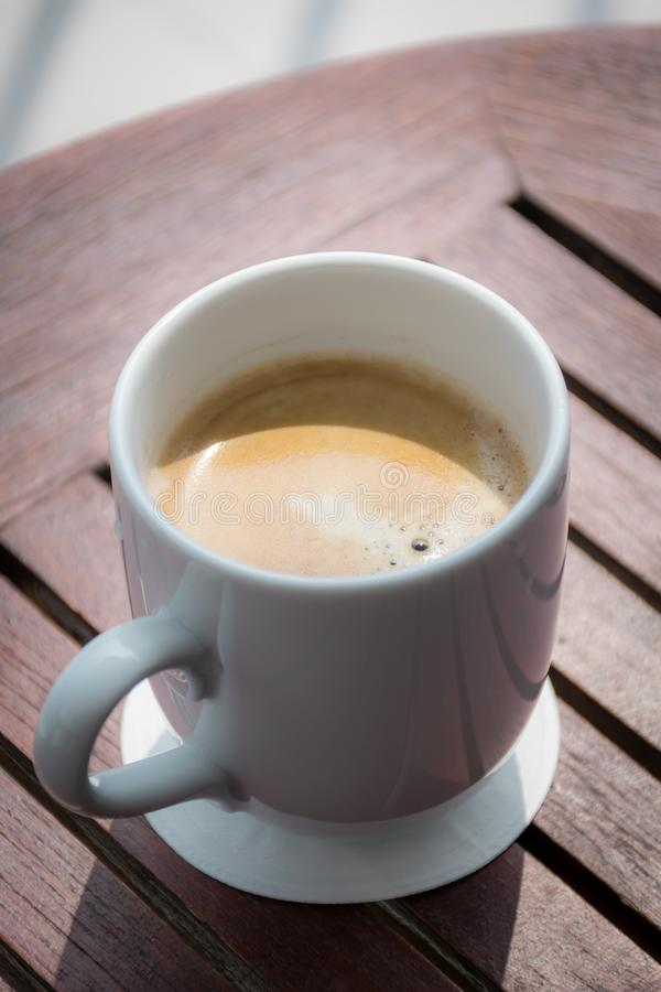 A cup of coffee on a wood table. royalty free stock photo