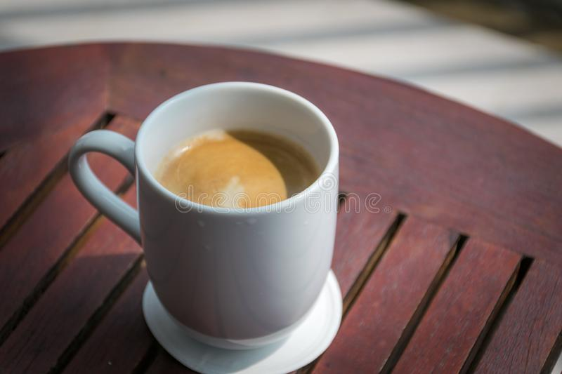 A cup of coffee on a wood table. stock images