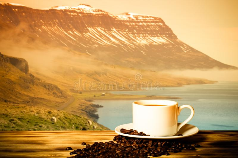 Coffee and white cup on the wooden table on the background of foggy landscape of the fjords of Iceland. Collage. Toned royalty free stock photography
