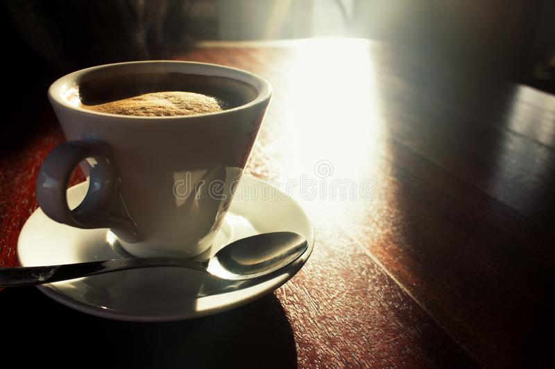 Coffee in white cup on wooden table in morning sunlight. Morning aroma coffee concept. White cup with plate and spoon in sunlight. stock photography