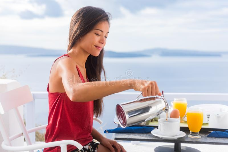 Coffee woman pouring tea in mug for breakfast at hotel room by Mediterranean sea on Europe vacation travel. Happy Asian girl royalty free stock images