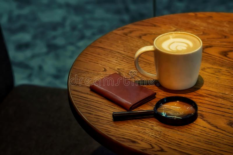 Coffee On a wooden table with wallet and magnifying glass is elements. Concept, content, lifestyle, evening, room, lighting, shadow, restaurant, brown stock image