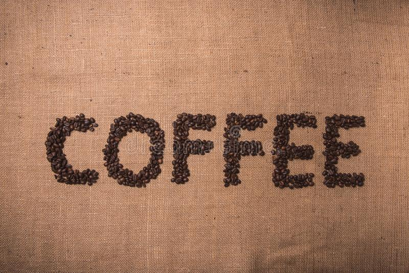 Coffee word with coffee beans. Coffee word written with toasted coffee beans on top view composition stock photos