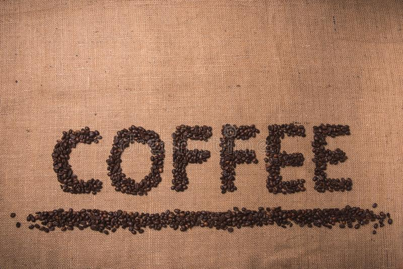 Coffee word with coffee beans. Coffee word written with toasted coffee beans on top view composition stock image