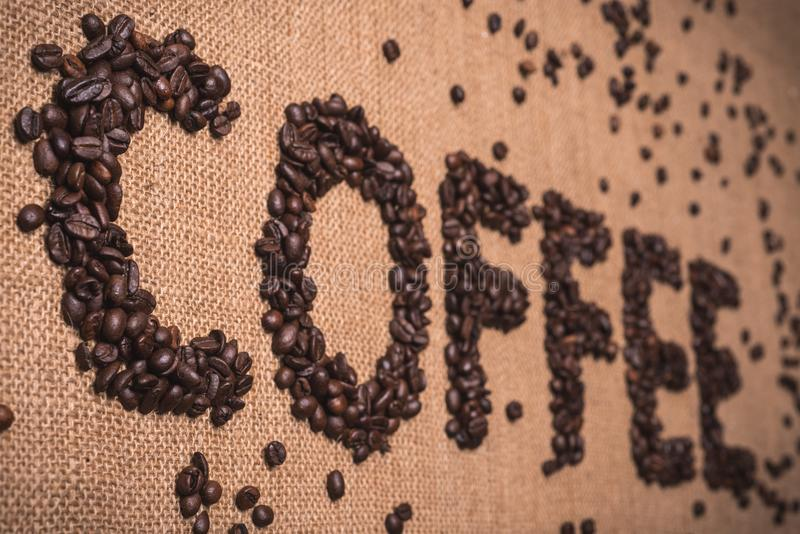 Coffee word with coffee beans. Coffee word written with toasted coffee beans on top view composition royalty free stock images