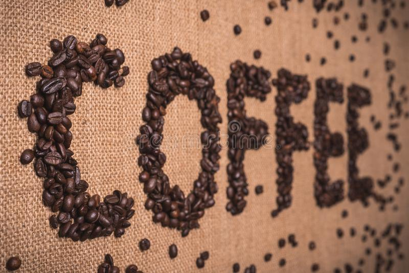 Coffee word with coffee beans. Coffee word written with toasted coffee beans on top view composition stock photography