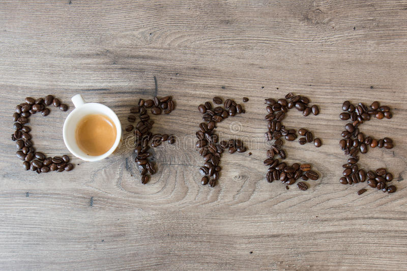 Coffee word made out of coffee beans and one espresso cup on top of a table. Coffee word made out of coffee beans and one espresso cup on top of a wooden table stock photography