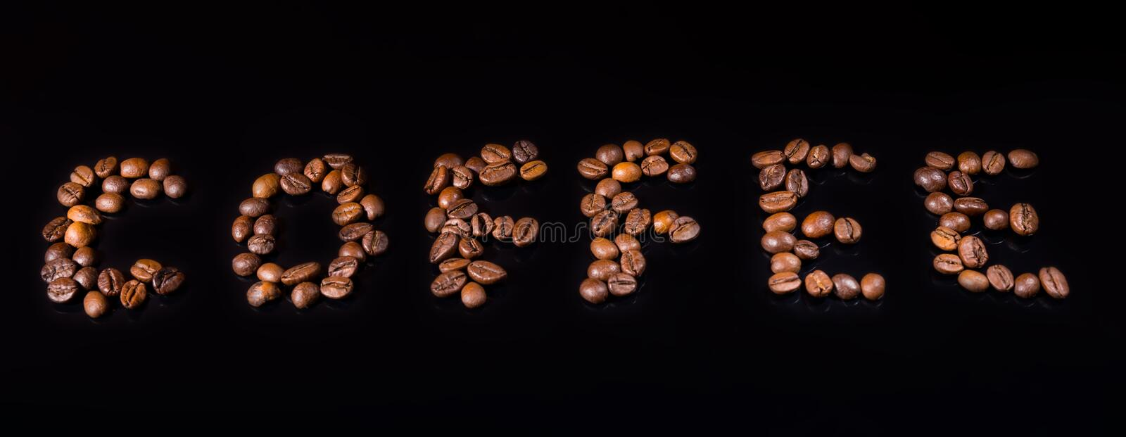 Coffee word made of roasted beans on black stock photography