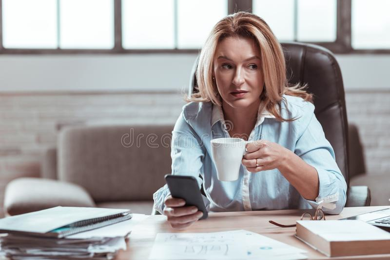 Beautiful lawyer feeling relaxed drinking some coffee at work royalty free stock photography