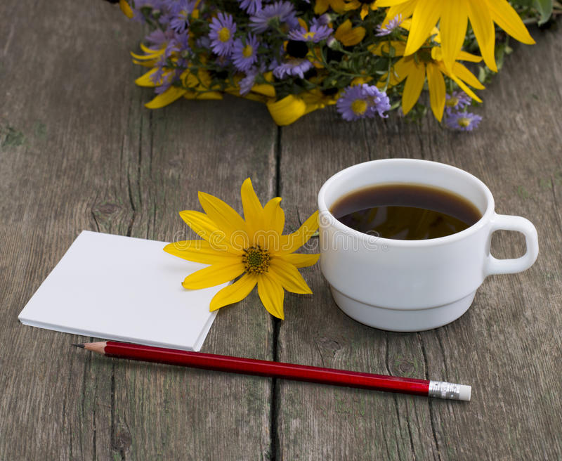 Coffee, yellow flower, pencil with paper and wild flowers, a sti. Ll life, a subject flowers and drinks stock photo