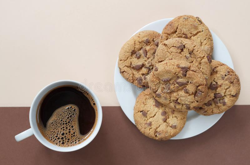 Coffee and yummy chocolate chips cookies. Cup of coffee and yummy chocolate chips cookies on two-color background, top view stock photos