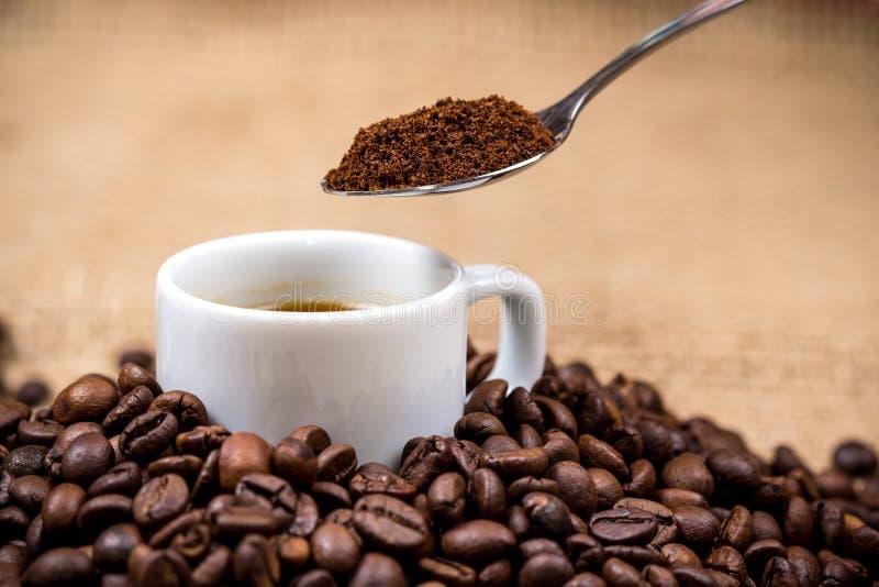 Coffeecup blanco en coffeebeans con la cuchara arriba foto de archivo libre de regalías