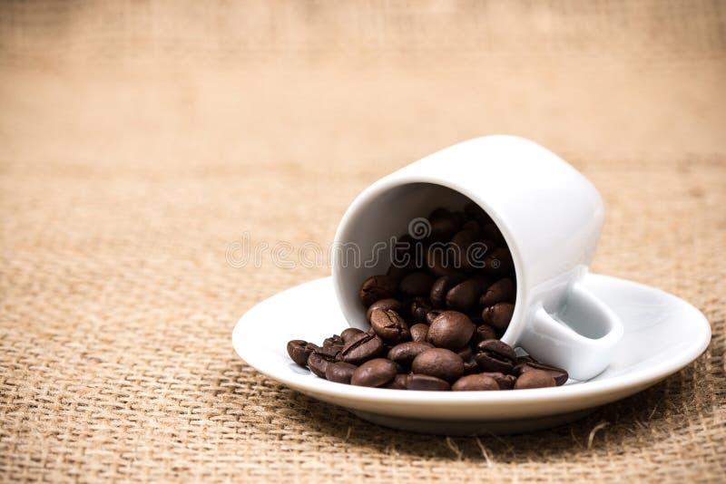 Coffeecup con los coffeebeans en la materia textil del yute foto de archivo libre de regalías