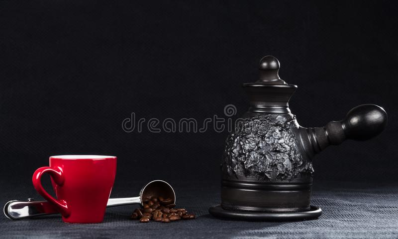 A coffeepot, cup and steel measuring spoon with coffee beans royalty free stock images