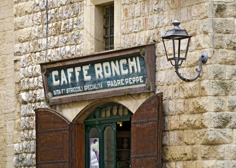 Coffeeshop at Altamura. ALTAMURA, ITALY - MAY 24, 2018: old name plate over the entrance to a coffee house in an old stone house royalty free stock images