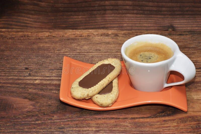 Coffekoppen och den lilla kakan på en lantlig trätabell royaltyfri bild