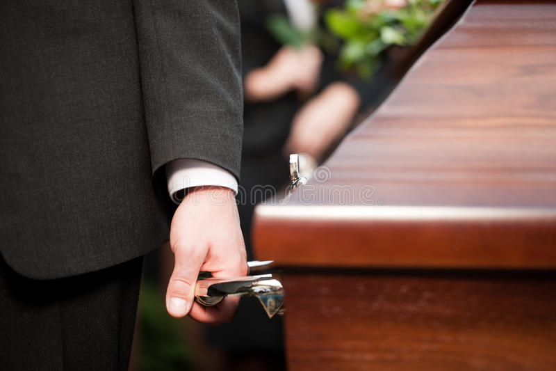 Coffin bearer carrying casket at funeral. Religion, death and dolor - coffin bearer carrying casket at funeral to cemetery royalty free stock photography