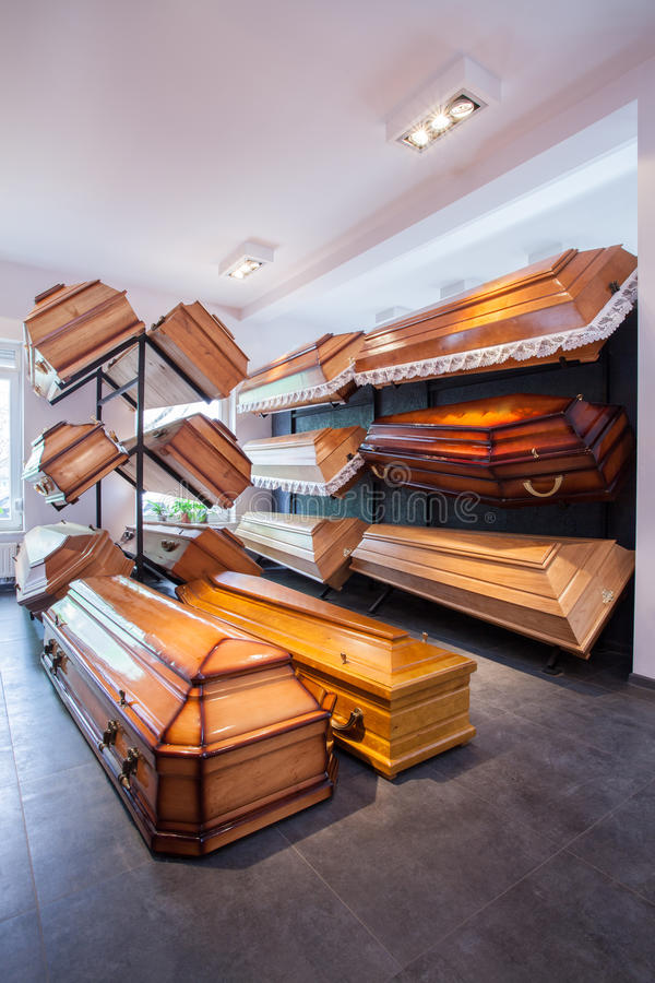 Coffins in funeral home. Wooden brown different coffins in funeral home stock photo