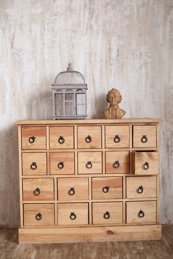 Coffre des tiroirs en bois dans la pièce dénommée minable avec la cage à oiseaux et images libres de droits