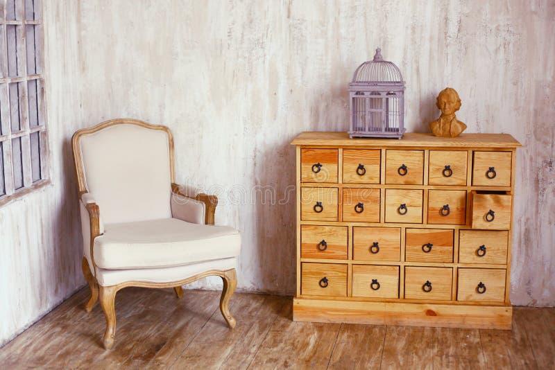 Coffre des tiroirs en bois dans la pièce dénommée minable avec la cage à oiseaux et photo libre de droits