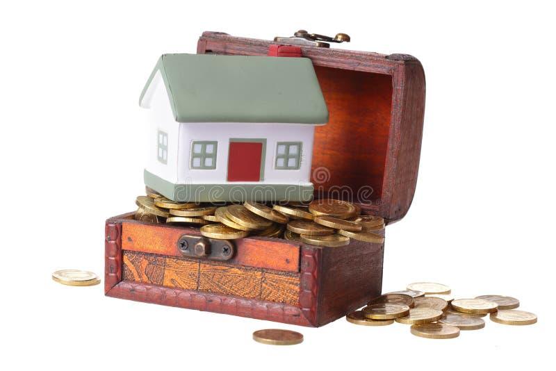 Coffre en bois avec des pièces de monnaie et une petite maison images stock