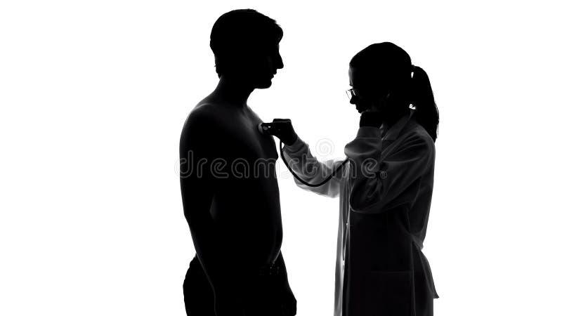 Coffre patient masculin de examen de thérapeute féminin avec le stéthoscope, soins de santé photographie stock