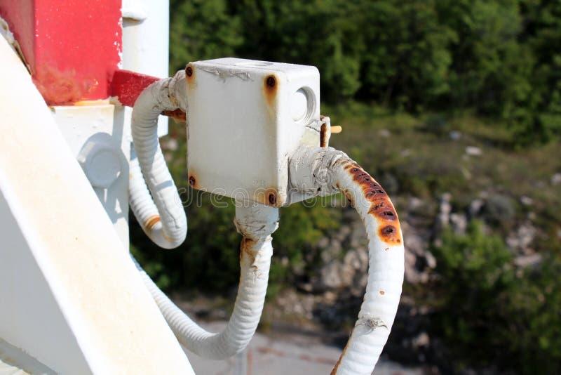 Coffret électrique extérieur en plastique avec trois fils endommagés reliés de tous les côtés montés sur le tuyau en métal avec d image libre de droits