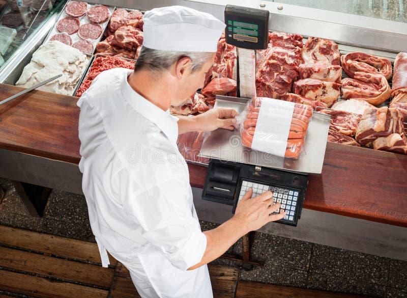 Coffret d'étalage de Weighing Sausages At de boucher photo stock