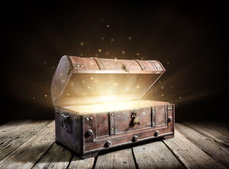 Cofre del tesoro - tronco antiguo abierto con las luces mágicas que brillan intensamente foto de archivo