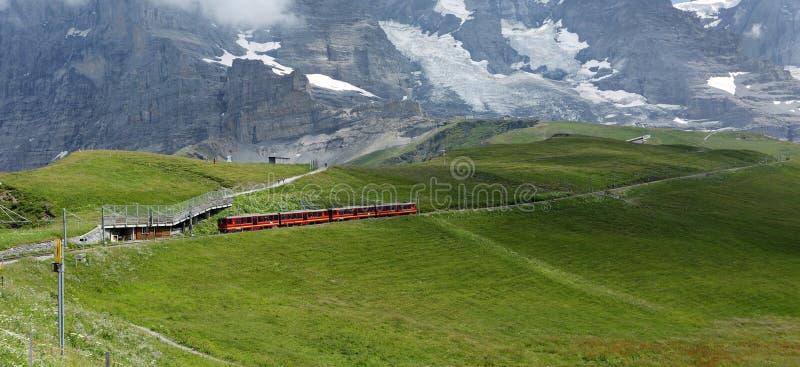 Cog Railway also called as rack railway or rack and pinion railway. KLEINE SCHEIDEGG, SWITZERLAND - JULY 24: Tourists traveling on Cog Railway from Kleine stock photography