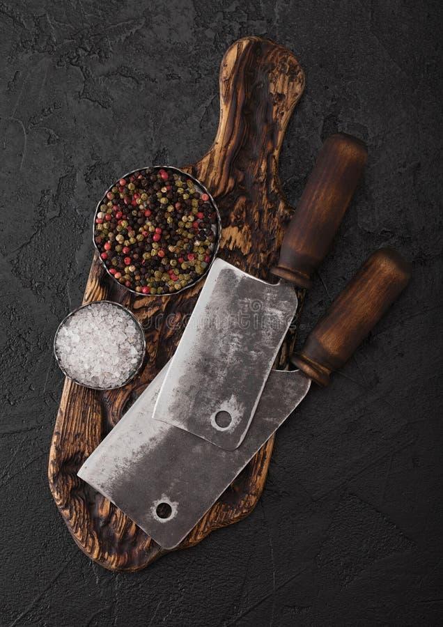 Cognées de couteau de viande de cru sur le hachoir de cru et le fond en pierre noir de table Ustensiles de boucher photos libres de droits