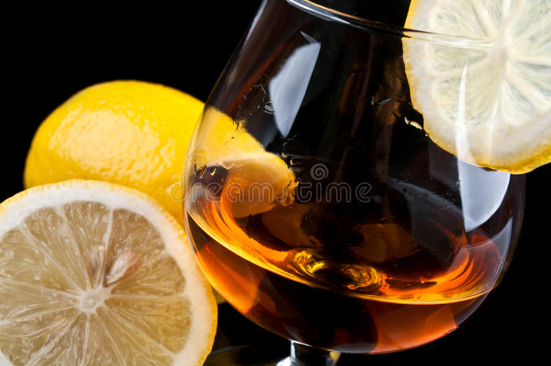Cognac avec le citron dans une glace classique images libres de droits