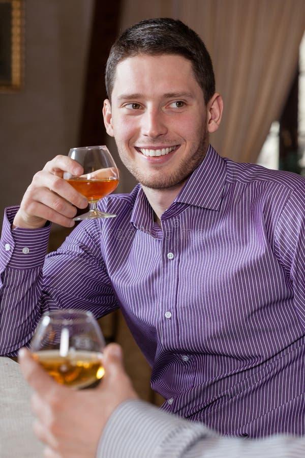 Cognac bevente dell'uomo con l'amico fotografie stock