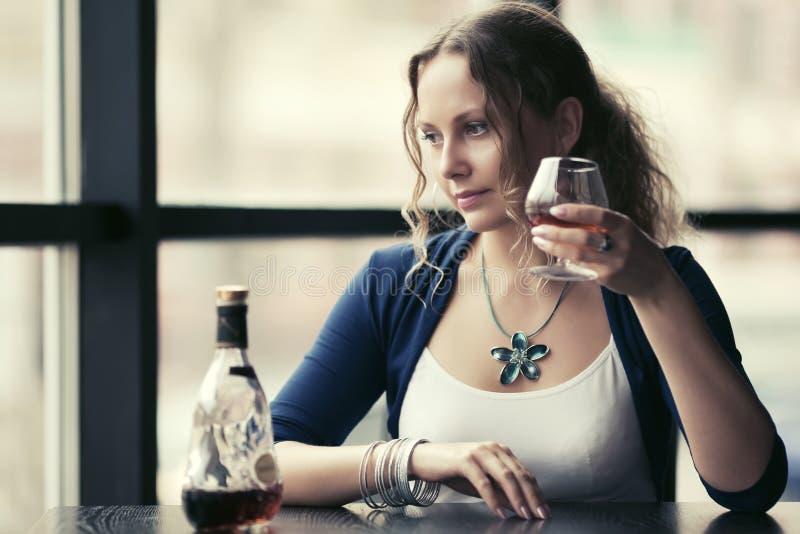 Cognac bevente della bella giovane donna immagini stock