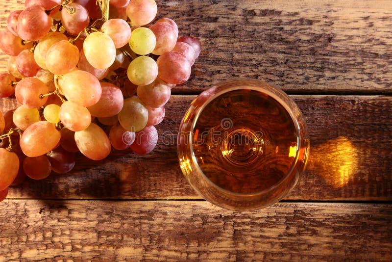 Cognac of Brandewijn in een glas en verse druiven, stilleven in rustieke stijl, uitstekende houten achtergrond, selectieve nadruk royalty-vrije stock fotografie