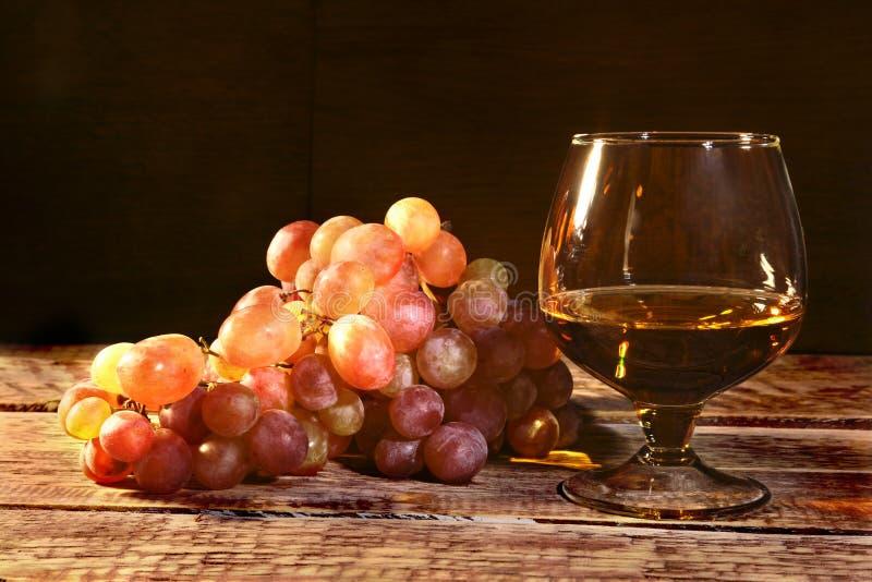 Cognac of Brandewijn in een glas en verse druiven, stilleven in rustieke stijl, uitstekende houten achtergrond, selectieve nadruk royalty-vrije stock afbeeldingen