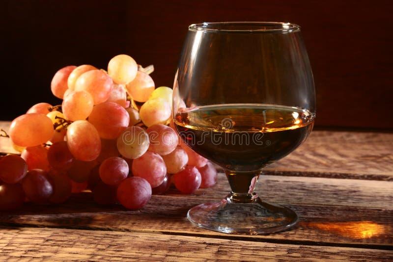 Cognac of Brandewijn in een glas en verse druiven, stilleven in rustieke stijl, uitstekende houten achtergrond, selectieve nadruk stock afbeeldingen