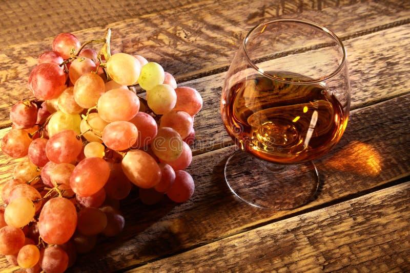 Cognac of Brandewijn in een glas en verse druiven, stilleven in rustieke stijl, uitstekende houten achtergrond, selectieve nadruk stock foto