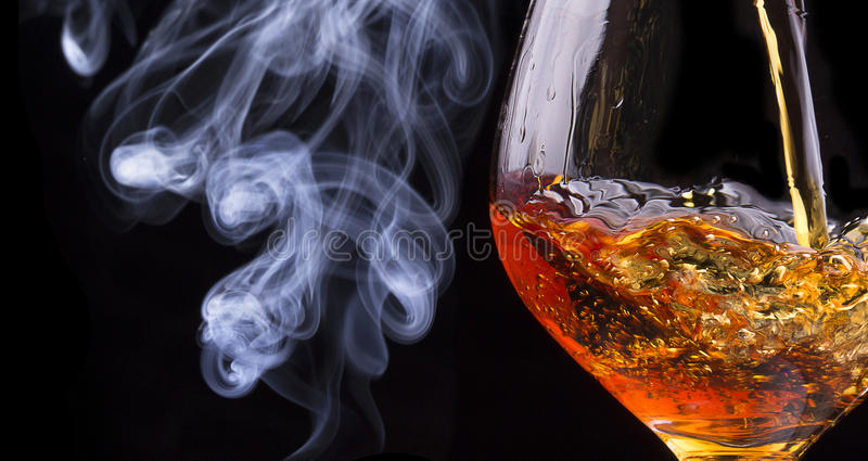 Cognac or brandy on a black with cigar smoke stock images