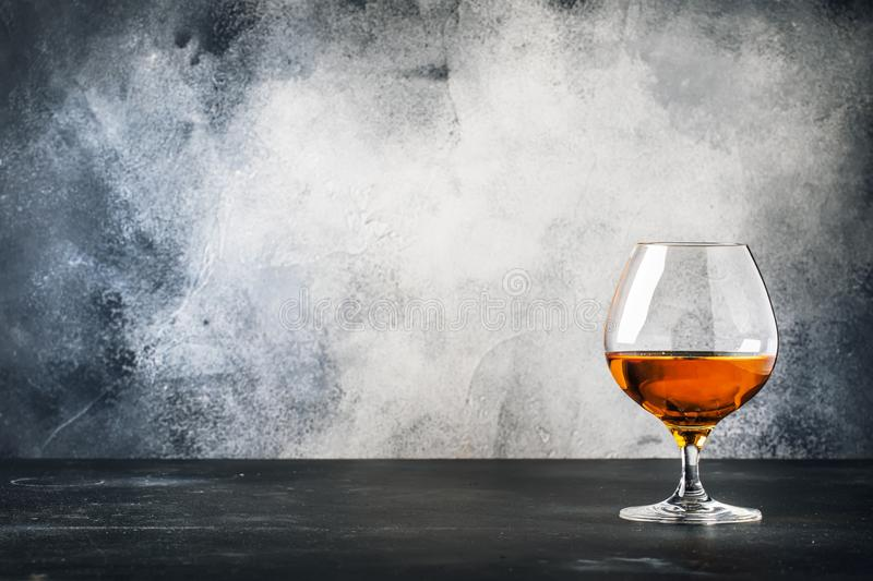 Cognac or brandy in wine glass, gray stone bar counter background, selective focus royalty free stock images