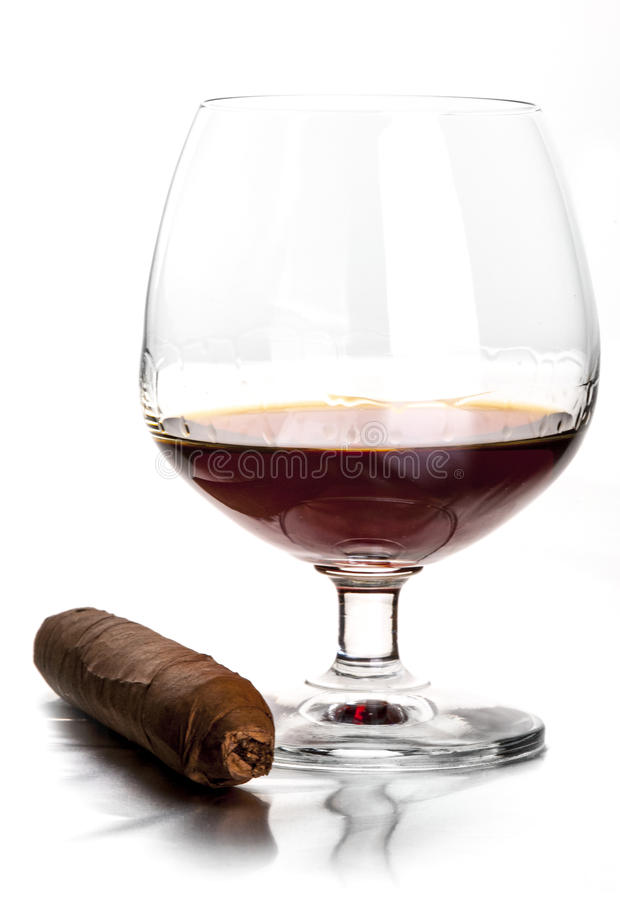 Cognac and cigar. Glass of cognac and cigar on the white background royalty free stock photos