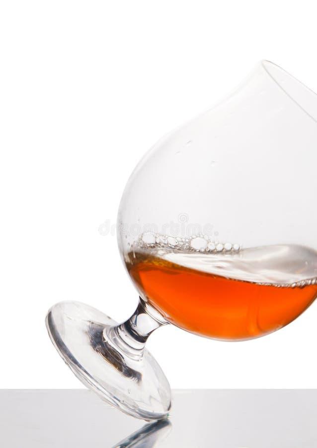 Cognac dans le verre à vin d'isolement sur le blanc photo stock