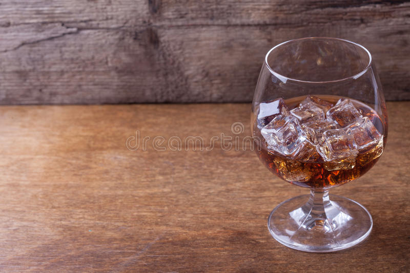 Cognac dans un verre avec de la glace sur le plan rapproché en bois de fond photographie stock