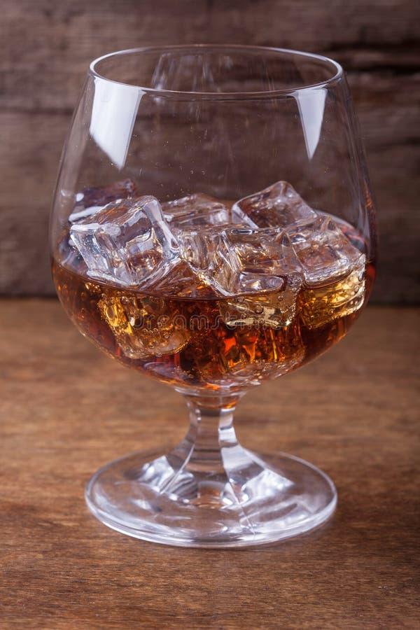 Cognac dans un verre avec de la glace sur le plan rapproché en bois de fond photo stock