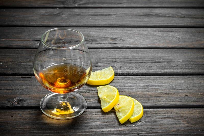 Cognac dans un verre avec des tranches de citron images libres de droits