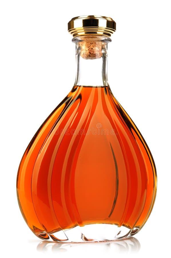 Cognac dell'alcool in una bottiglia chiusa su bianco fotografia stock