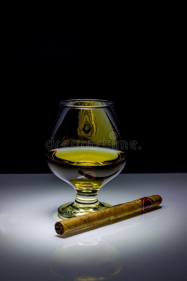 Cognac e sigaro su un fondo nero fotografia stock libera da diritti