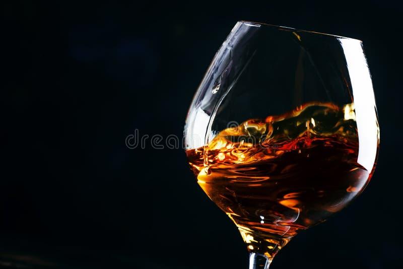 Cognac in een glas, donkere achtergrond, selectieve nadruk royalty-vrije stock afbeelding