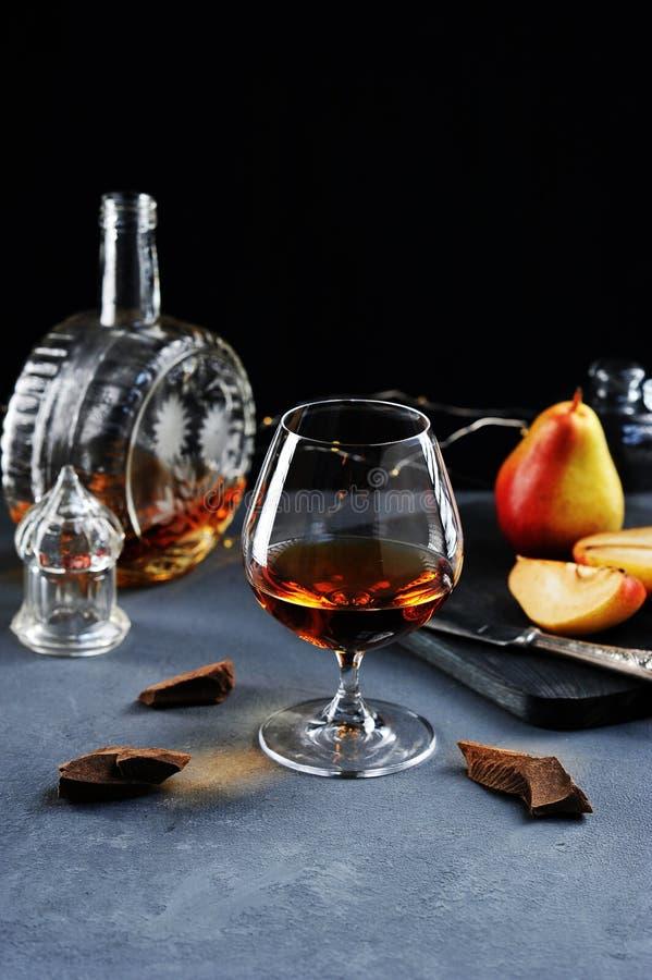 Cognac in een glas met chocolade en peer stock foto's